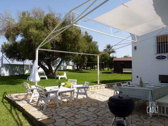Terraza trasera con mesas, sillas y Barbacoa Webber